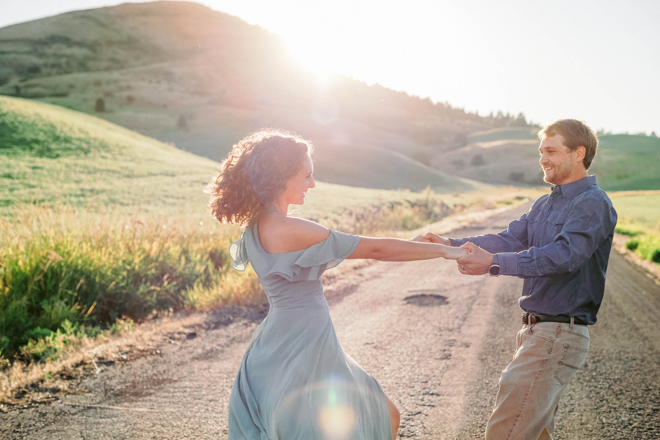 sunflare peeping over rolling hill with vibrant green grass as a couple spins hand in hand, girl with curly hair and green flowy dress, man in a blue denim shirt and kahki pants