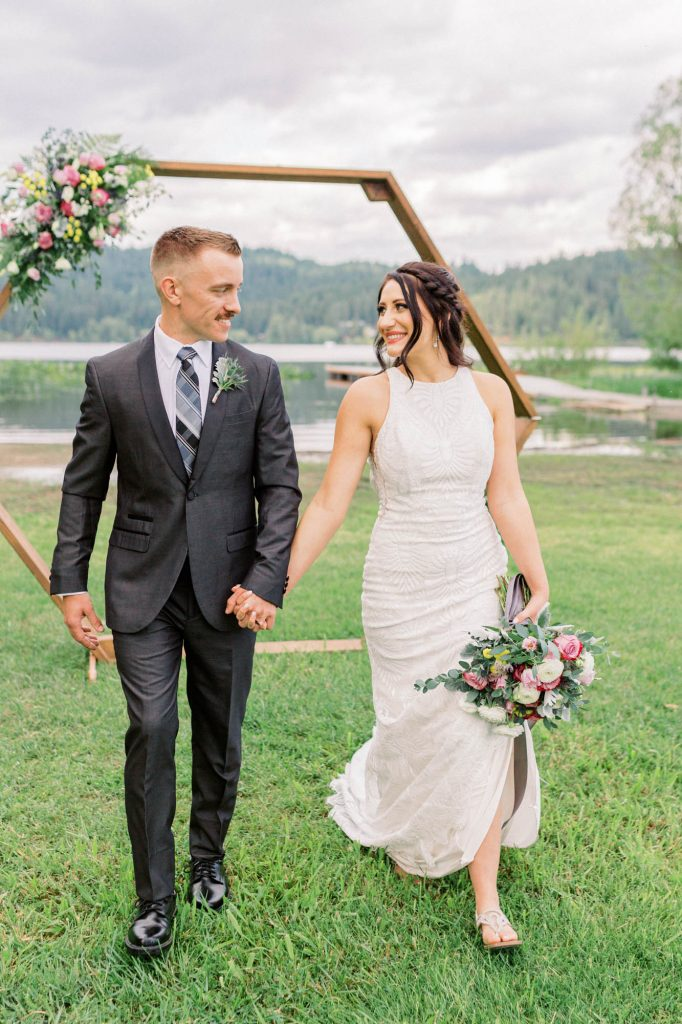 groom in a gray suit holding hands as he walks with bride in lace dress holding a bouquet with pink and yellow florals in front of a wood hexagon arch at the beach at hauser lake farms wedding venue photo captured by spokane wedding photographer rachel jordan photography
