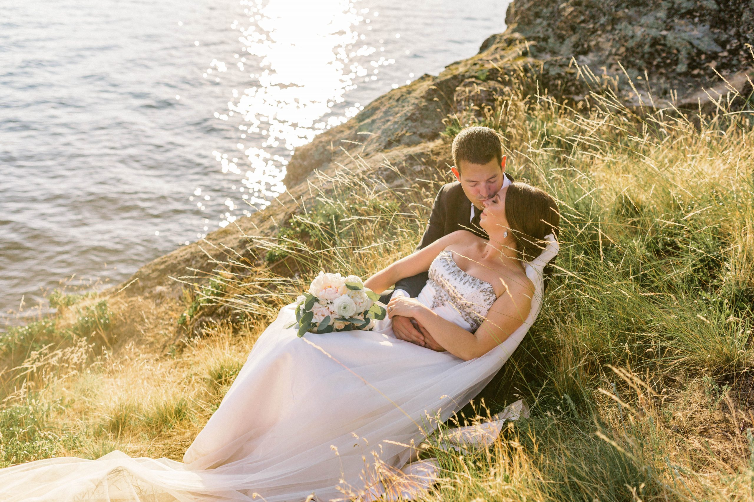 sun glistening on the water of lake coeur d'alene as a bride with a beaded strapless dress and long veil reclines with groom in the tall grass above the shoreline shot by wedding photographer rachel jordan