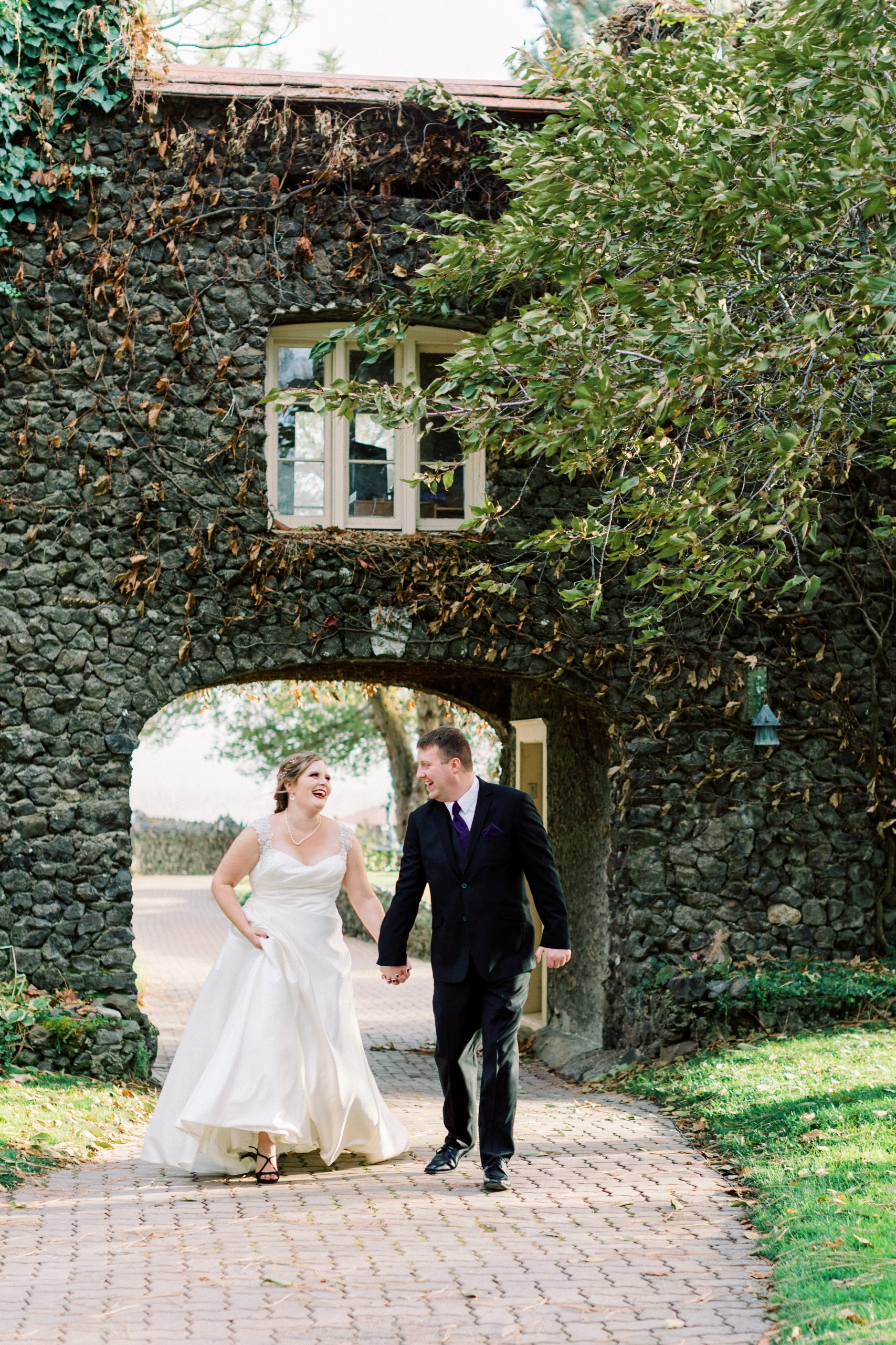Bride and groom laughing as they walk under a beautiful stone arch at arbor crest winery in spokane captured by spokane wedding photographer rachel jordan photography