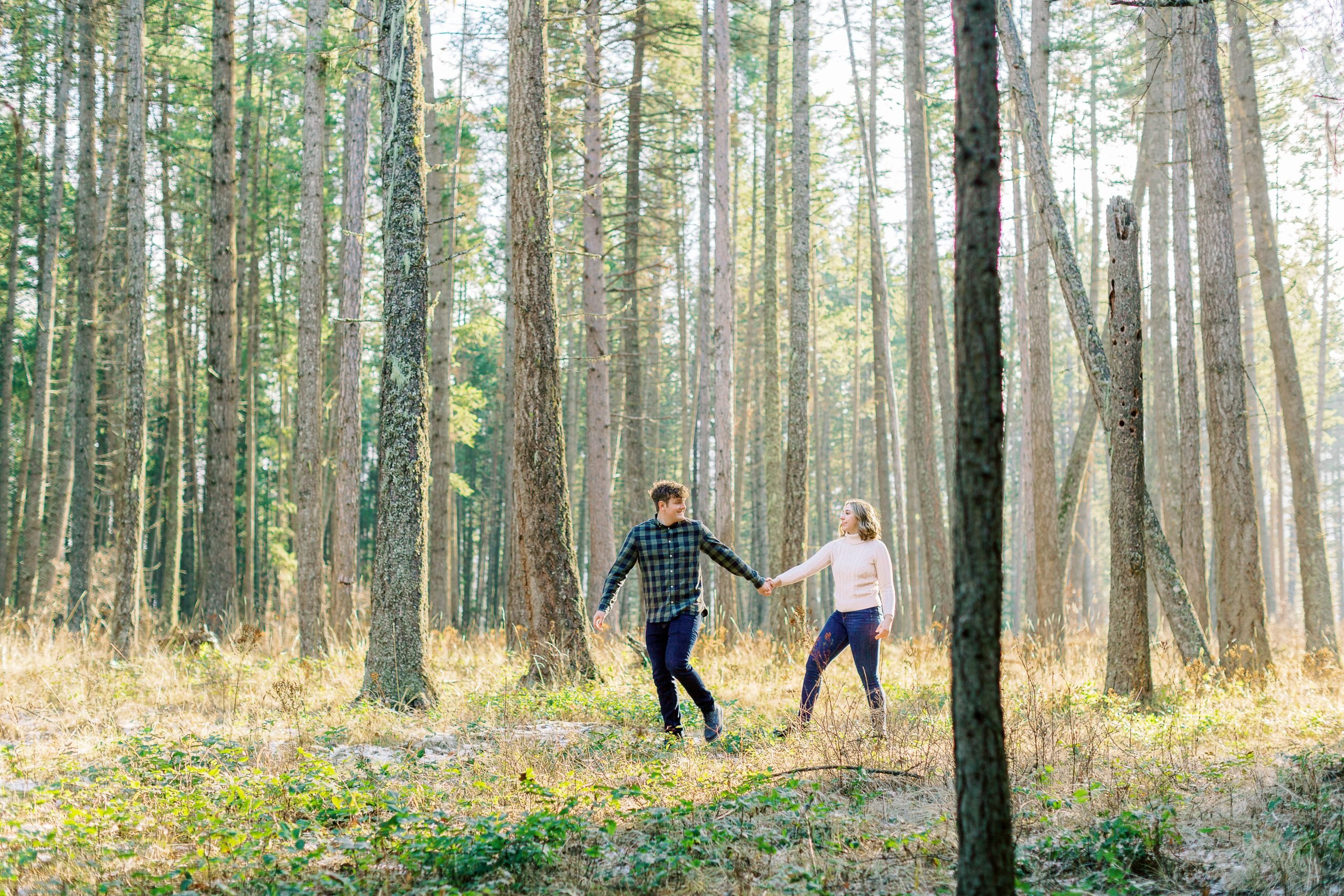 man in green plaid shirt leads fiancee in white sweater through beautiful woods with the sun streaming through the trees at Farragut State Park in north idaho shot by idaho wedding photographer rachel jordan photography